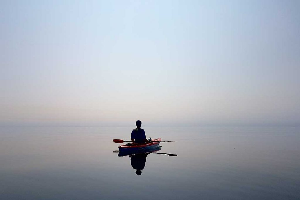 person in kayak on flat water