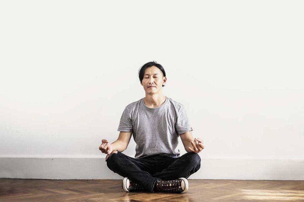 male in jeans sitting cross legged